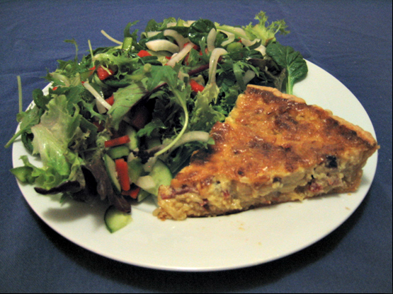 A slice of onion tart served with salad