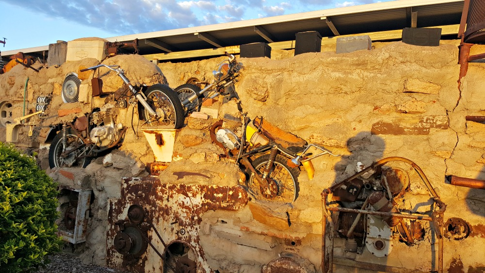 Sunrise hitting some motorbikes embedded in Arno's Wall.